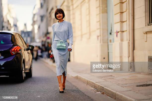 Patricia Gloria Contreras wears a blue dress and a green bag outside Jacquemus during Paris Fashion Week Womenswear Spring/Summer 2019 on September...