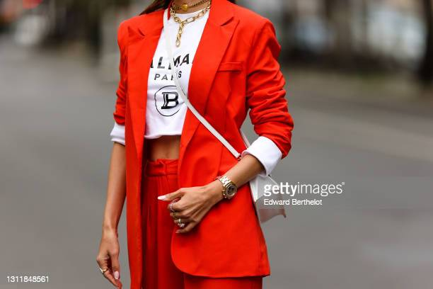 Patricia Gloria Contreras wears a Chanel golden necklace / choker, a Rolex watch, an orange / red blazer oversized jacket from Nastygal, flared suit...