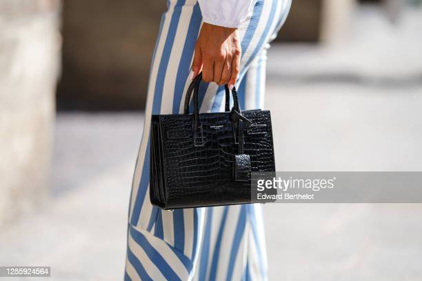 Patricia Gloria Contreras wears blue and white striped pants, a Saint Laurent YSL black crocodile pattern leather bag, on July 09, 2020 in Paris,...