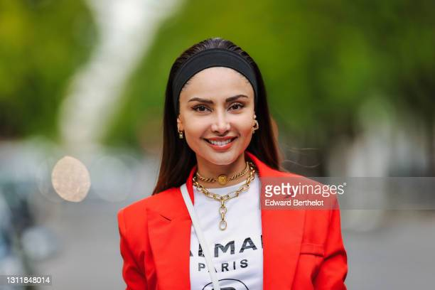 Patricia Gloria Contreras wears earrings, a bandanna, a Chanel golden choker, a golden chain necklace, an orange / red blazer oversized jacket from...