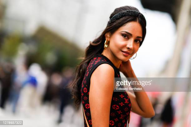 Patricia Gloria Contreras wears earrings, a headband, a sleeveless black and red Vuitton monogram print pullover,outside Louis Vuitton, during Paris...