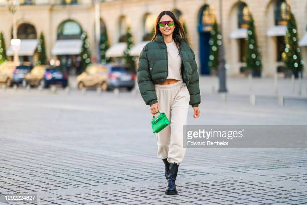 Patricia Gloria Contreras wears neon colored shiny sunglasses from Quay, a green winter bomber puffer jacket from Nastygal, a white cropped top from...