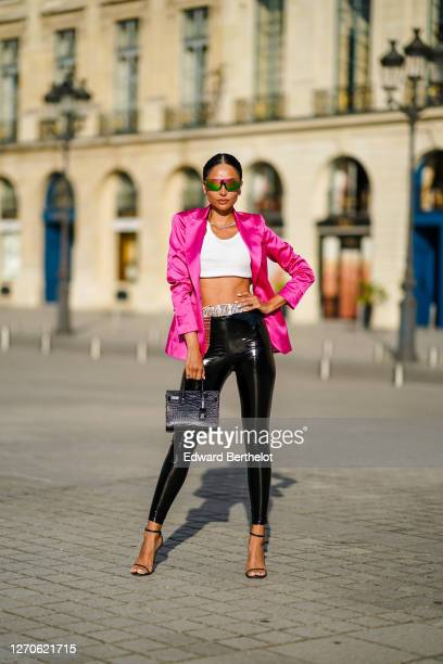 Patricia Gloria Contreras wears Stewart Weitzman high heels shoes, a black leather crocodile pattern bag from YSL Saint-Laurent, black shiny vinyl...