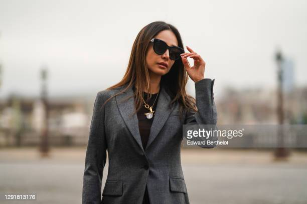 Patricia Gloria Contreras wears sunglasses, a golden necklace, a black mesh top, a gray blazer jacket from Parosh, on December 09, 2020 in Paris,...