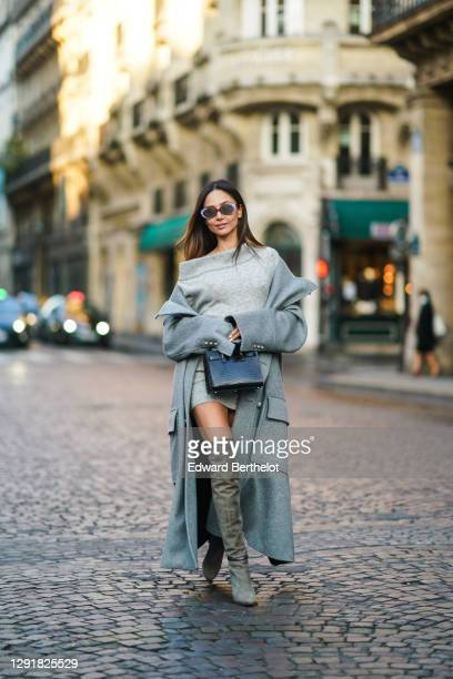 Patricia Gloria Contreras wears sunglasses, a gray long coat with large pockets from Balmain, a one-off-shoulder wool oversized long pullover worn as...