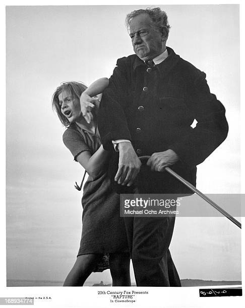Patricia Gozzi is frighten as she stands behind Melvyn Douglas for protection in a scene from the film 'Rapture' 1965