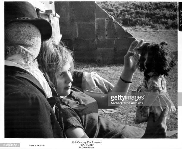 Patricia Gozzi leaning into a scarecrow while playing with a doll in a scene from the film 'Rapture' 1965