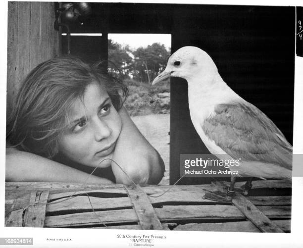 Patricia Gozzi looking at the bird that is standing on the fence in a scene from the film 'Rapture' 1965