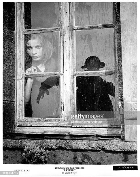 Patricia Gozzi looking out the window at a scarecrow in a scene from the film 'Rapture' 1965