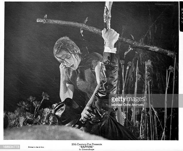 Patricia Gozzi standing in the field in pouring rain helping a man on the ground in a scene from the film 'Rapture' 1965