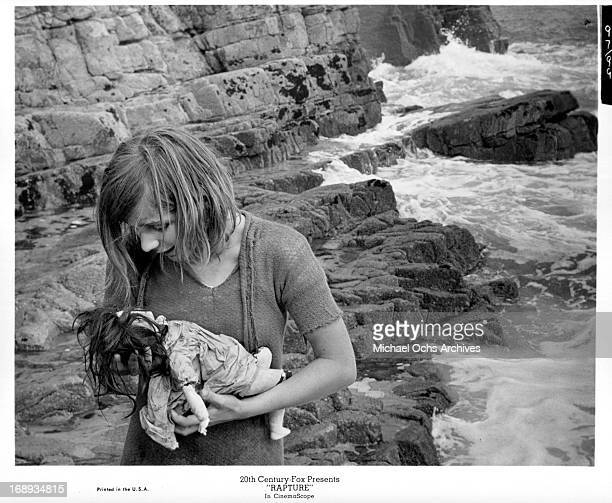 Patricia Gozzi talking to her doll as she stands on rocks at the beach while the water washes up around her in a scene from the film 'Rapture' 1965
