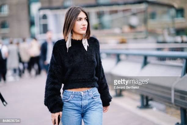 Patricia Manfield wears a black faux fur sweater blue denim jeans outside Versus during London Fashion Week September 2017 on September 17 2017 in...