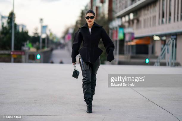 Patricia Manfield wears sunglasses, a jacket with oversized sleeves, black leather pants, pointy high boots, a bag, outside Jacquemus, during Paris...
