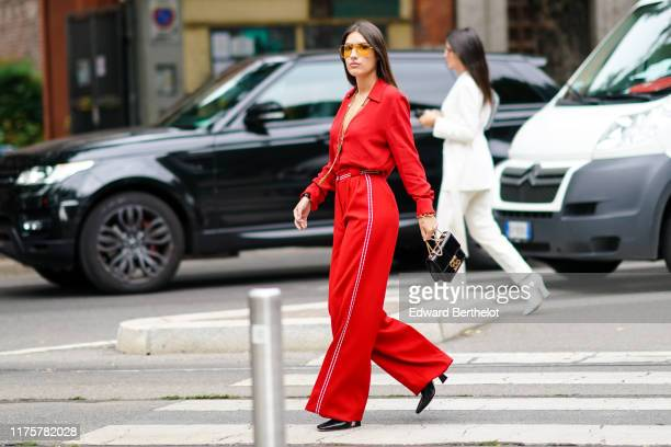 Patricia Manfield wears sunglasses, a red low neck top, flared pants, a bag, a necklace, outside the Fendi show during Milan Fashion Week...