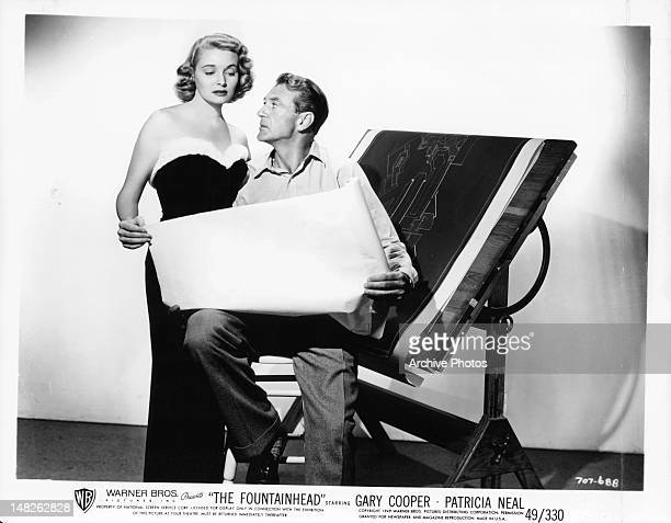 Patricia Neal and Gary Cooper looking at blueprints in publicity portrait for the film 'The Fountainhead', 1949.