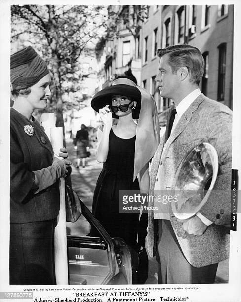 Patricia Neal converses with George Peppard while Audrey Hepburn looks over her sunglasses in a scene from the film 'Breakfast At Tiffany's' 1961