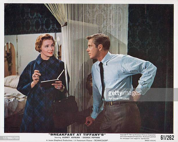 Patricia Neal writing in book while talking with George Peppard in a scene from the film 'Breakfast At Tiffany's' 1961