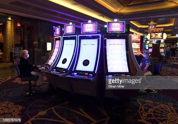 Patricia Sanchez of California and Armando Alvarado of Illinois wear masks as they play slot at sociallydistanced slot machines at Mandalay Bay...
