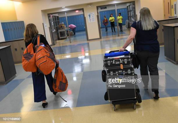 Patricia Shaw left and Abigail Molina both interpreters for Aurora Public Schools arrive with transmitters and headsets to be used during a welcome...