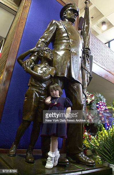 Patricia Smith, 2 1/2, the daughter of Police Officer Moira Smith, plays on statue in the lobby of police headquarters during ceremony to honor...