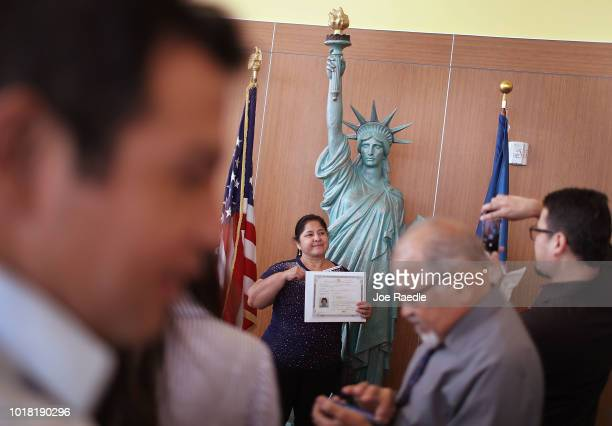 Patricia Tabares orginally from Columbia poses for a family picture in front of a replica of the Statue of Liberty after participating in a ceremony...