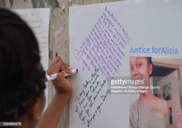 Patricia Todd writes a message to her slain sister Alicia Todd as she gathers at the spot where Alicia was killed last year in Long Beach CA on...