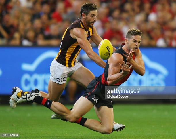 Patrick Ambrose of the Bombers handballs away from Ricky Henderson of the Hawks during the round one AFL match between the Essendon Bombers and the...