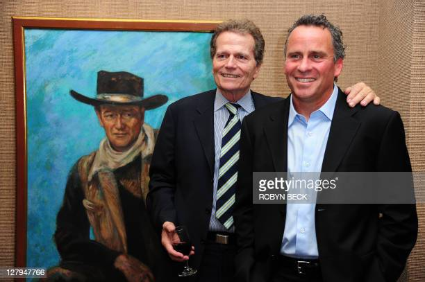 Patrick and Ethan Wayne sons of the iconic American film star John Wayne pose beside a painting of their father at an auction preview October 3 2011...