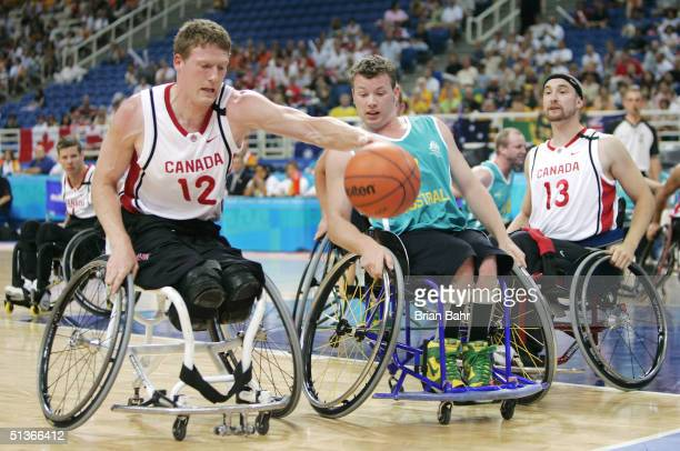 Patrick Anderson of Canada reaches out to grab a loose ball in front of Shaun Norris of Australia during their gold medal wheelchair basketball game...