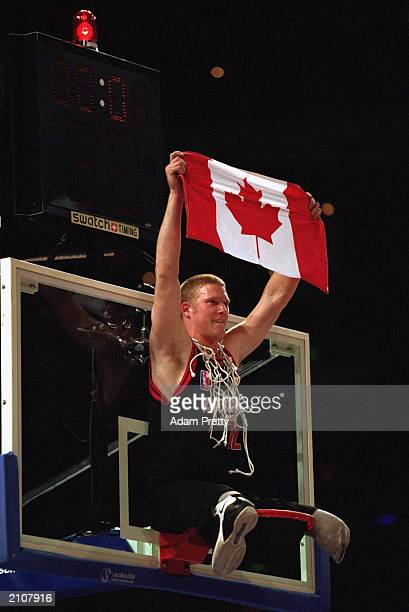 Patrick Anderson of Canada sits on the hoops in celebration as he holds up a Canadian flag after winning the Men's Wheelchair Basektball Gold Medal...