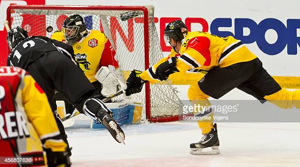 Patrick Asselin of Soenderjyske scores to 4-4 against Tomas Duba of Krefeld Pinguine during the Champions Hockey League group stage game between...