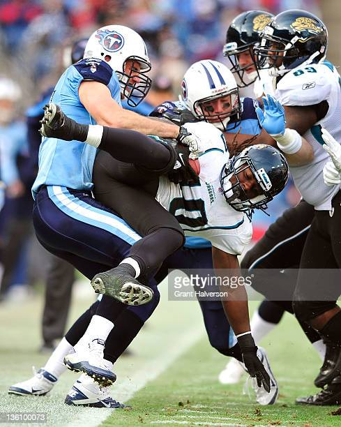 Patrick Bailey of the Tennessee Titans tackles DuJuan Harris of the Jacksonville Jaguars during play at LP Field on December 24 2011 in Nashville...