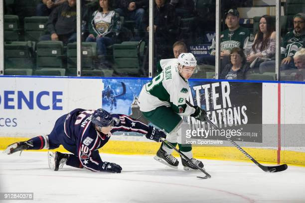 Patrick Bajkov of the Everett Silvertips keeps the puck out of reach of TriCity Americans defenseman Dylan Coghlan in a game between the Everett...