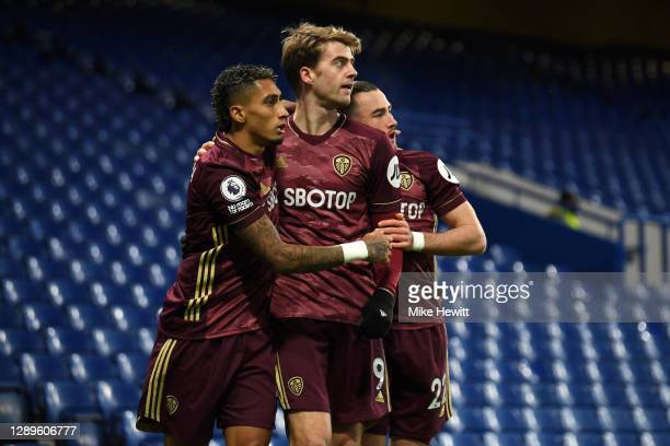 Patrick Bamford of Leeds United celebrates with teammates Jack Harrison and Raphinha after scoring their team's first goal during the Premier League...