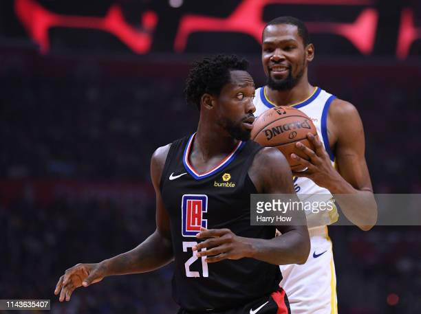 Patrick Beverley of the LA Clippers looks back at a smiling Kevin Durant of the Golden State Warriors during Game Two of Round One of the 2019 NBA...