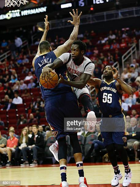 Patrick Beverley of the Houston Rockets passes around Alexis Ajinca of the New Orleans Pelicans as E'Twaun Moore looks on at Toyota Center on...