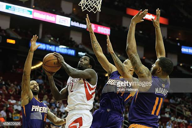 Patrick Beverley of the Houston Rockets takes a shot as he is defended by Marcus Morris Gerald Green and Markieff Morris of the Phoenix Suns at...