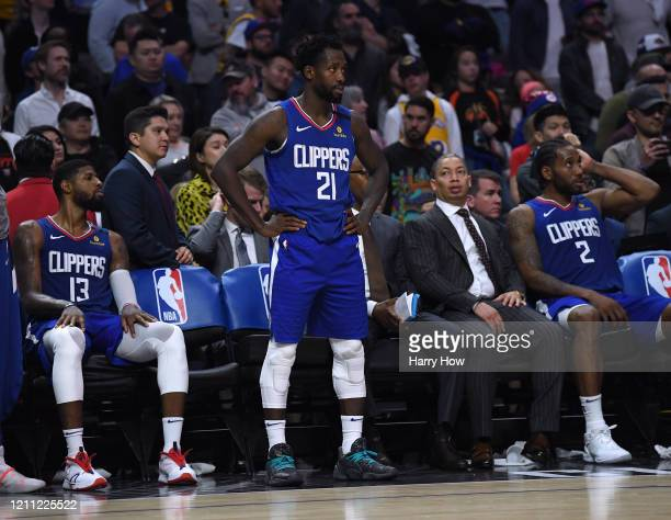 Patrick Beverley, Paul George and Kawhi Leonard of the LA Clippers watch during a 112-103 LA Clippers win at Staples Center on March 08, 2020 in Los...