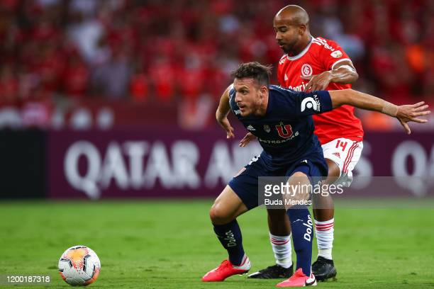 Patrick Bezerra of Internacional struggles for the ball with a Angelo Henriquez of Universidad de Chile during a match between Internacional and...