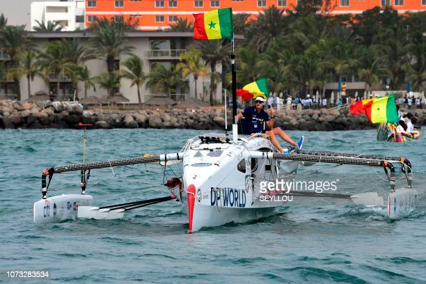 Patrick Bol Dutch skipper of the Row4ocean rowing trimaran holds a Senegalese flag as his team leaves Dakar to cross the Atlantic on December 14 2018...