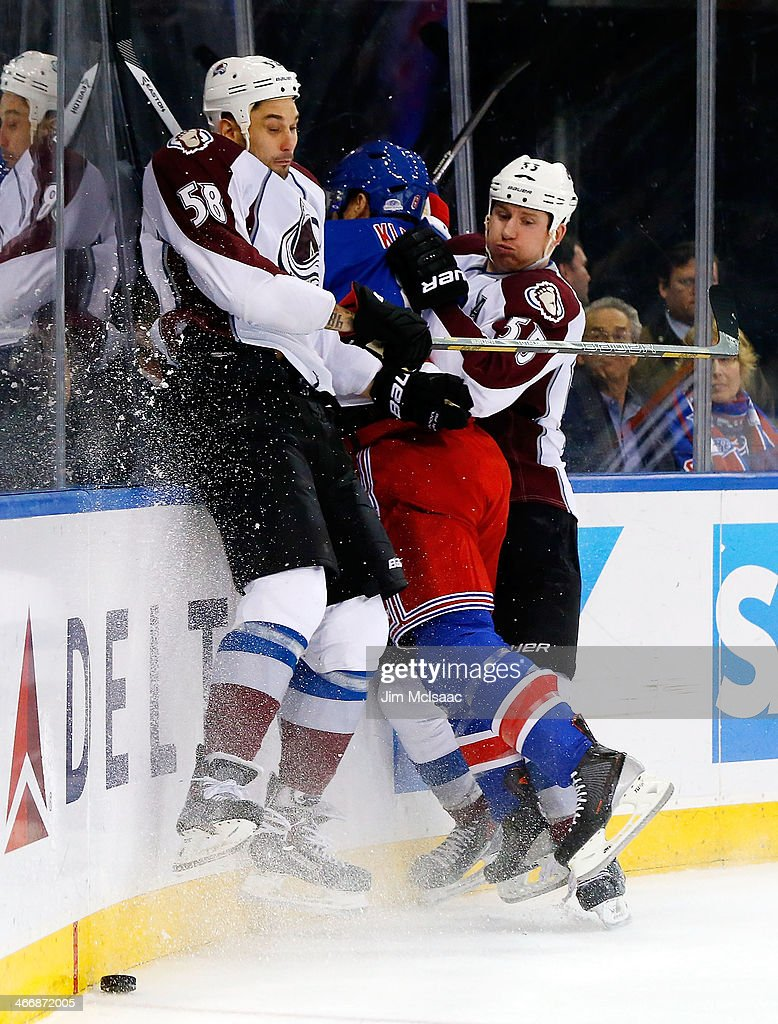 Patrick Bordeleau #58 and Cody McLeod #55 of the Colorado Avalanche team up for a hit against Kevin Klein #8 of the New York Rangers at Madison Square Garden on February 4, 2014 in New York City.