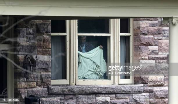 Patrick Boyle father of freed Canadian hostage Joshua Boyle puts up a bedsheet to block the view of journalists camped outside the Boyle family home...