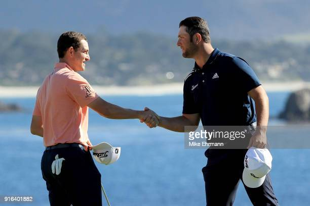 Patrick Cantlay and Jon Rahm of Spain meet after finishing their rounds on the 18th green during Round Two of the ATT Pebble Beach ProAm at Pebble...