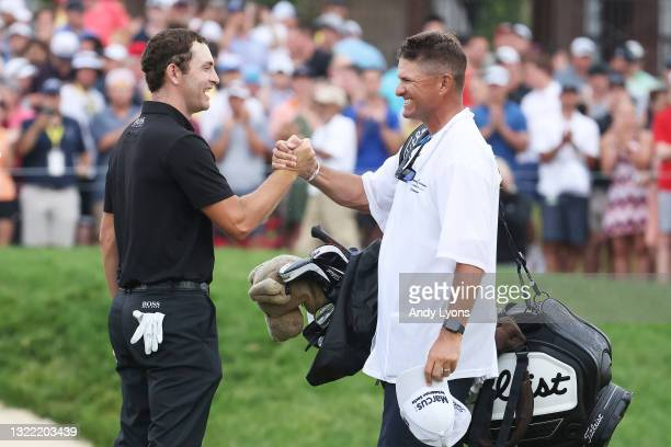 Patrick Cantlay of the United States celebrates with his caddie, Matt Minister, on the 18th green after winning the The Memorial Tournament in the...