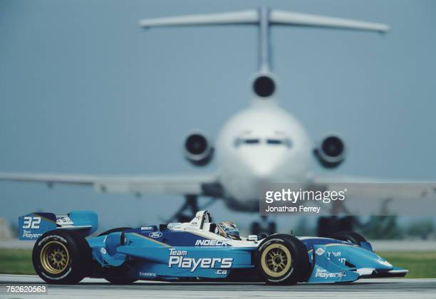 Patrick Carpentier of Canada drives the Player's Forsythe Racing Reynard 01i Ford XF V8t passes the FedEx transport aircraft during practice for the...