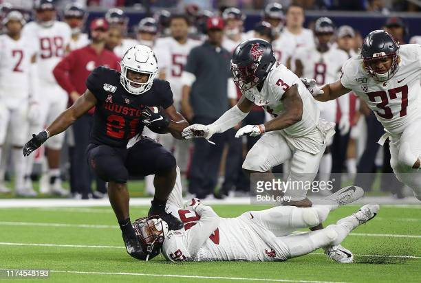 Patrick Carr of the Houston Cougars is tackled by Bryce Beekman of the Washington State Cougars as Daniel Isom assists during the first half of the...