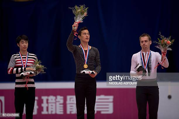 Patrick Chan of Canada celebrates with the gold medal on the podium after he won the men's free skating alongside Boyang Jin of China who won silver...