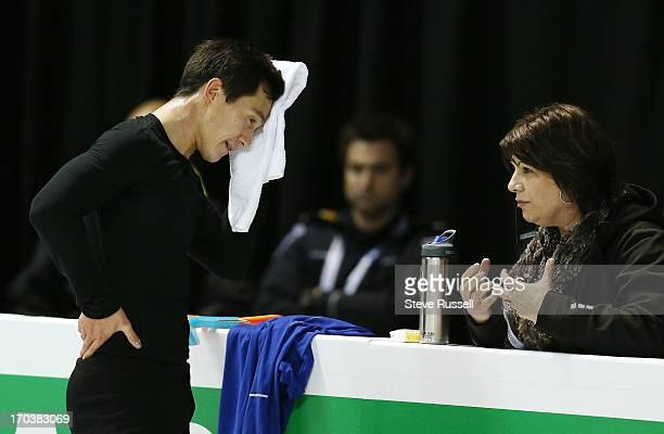 Patrick Chan talks to his coach Kathy Johnson as skaters practice their long routine as skaters prepare to compete in the ISU World Figure Skating...