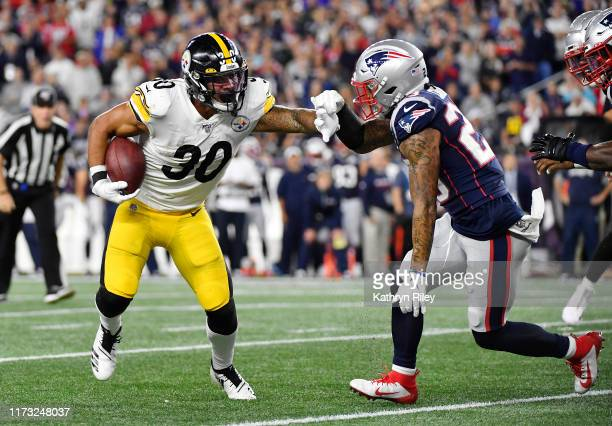 Patrick Chung of the New England Patriots attempts to tackle James Conner of the Pittsburgh Steelers during the second half at Gillette Stadium on...