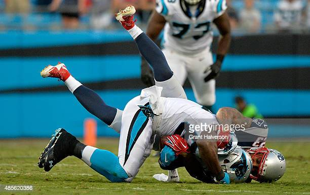 Patrick Chung of the New England Patriots tackles Jerricho Cotchery of the Carolina Panthers in the 1st quarter during their preseason NFL game at...